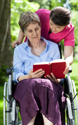 elder woman reading book and nurse assisting her